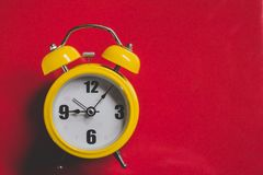 Retro yellow alarm clock with Nine Five Minutes Old Style, Top View on Red royalty free stock photos