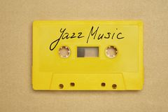 Retro yellow audio cassette tape with jazz music laying on the paper background. Retro yellow audio cassette tape with jazz music laying on the paper background royalty free stock photos