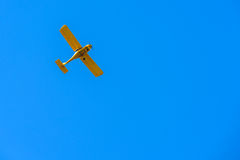 Retro yellow colored biplane flying against blue sky Stock Photos