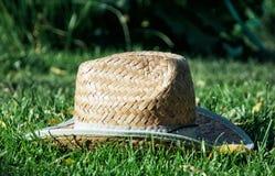 Retro yellow straw hat in the grass. Yellow straw hat in the grass. Rural symbol Stock Photos