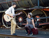 Retro young love couple vintage serenade train setting Royalty Free Stock Image