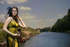 Retro young woman  with camera near the river Royalty Free Stock Photography