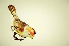 Retro- Zinnspielzeugvogel auf einem Retro- Hintergrund Stockbilder