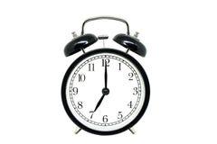 Retro zwarte wekker die zeven die uur tonen op witte achtergrond worden geïsoleerd stock foto