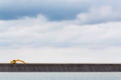 Retroexcavadora en cresta de la presa Fotografía de archivo libre de regalías
