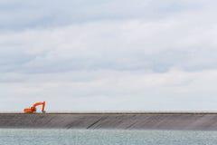 Retroexcavadora en cresta de la presa Imagen de archivo