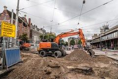 Retroexcavadora que repara las pistas de la tranvía en las calles de Amsterdam al día nublado y lluvioso imagen de archivo
