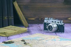 Retrostil Alte Bücher und eine Karte auf dem Tisch Filmkamera und eine Handvoll Münzen Lizenzfreies Stockfoto