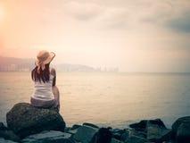 Retrostil der einsamen und deprimierten Frau, die vor dem Meer in einem einsamen Strand sitzt lizenzfreie stockbilder