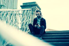 Retrostilfoto eines Hippie-Mannes, der sein Telefon überprüft Stockfotografie