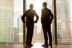 Retrovisione agli uomini d'affari africani e caucasici che stanno vicino alla vittoria Immagine Stock
