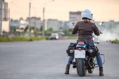 Retrovisione al motociclista della giovane donna pronto alla guida di stard sul motociclo sulla strada asfaltata, spazio della co fotografie stock
