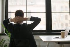 Retrovisione all'uomo d'affari rilassato che gode della rottura che riposa dal wor Fotografie Stock