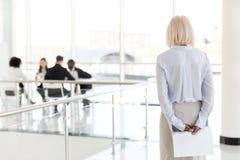 Retrovisione alla donna di affari senior nervosa sollecitata i aspettante immagini stock