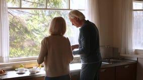 Retrovisione alle coppie senior che godono della cottura insieme nella cucina video d archivio