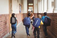 Retrovisione degli allievi felici che camminano al corridoio Immagine Stock
