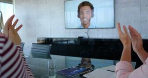 Retrovisione degli uomini d'affari razza mista che applaudono all'estremità di un video di conferenza in moderno di stock footage