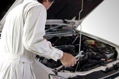 Retrovisione del meccanico automobilistico in uniforme di bianco con la chiave che diagnostica motore sotto il cappuccio al garag immagine stock