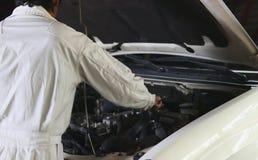 Retrovisione del meccanico automobilistico in uniforme di bianco con la chiave che diagnostica motore sotto il cappuccio al garag immagini stock libere da diritti