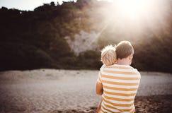 Retrovisione del padre con una condizione del ragazzo del bambino sulla spiaggia sulla vacanza estiva al tramonto fotografie stock libere da diritti