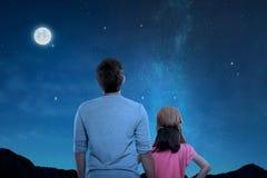 Retrovisione del padre e di piccola figlia che esaminano scena di notte fotografia stock libera da diritti