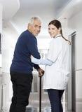 Retrovisione del paziente felice del dottore Walking With Senior Immagine Stock