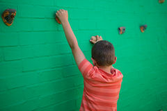 Retrovisione del ragazzo che scala sulla parete Immagini Stock Libere da Diritti