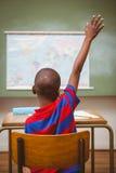 Retrovisione del ragazzo che solleva mano in aula Immagine Stock Libera da Diritti