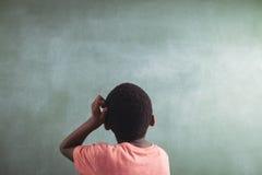 Retrovisione del ragazzo premuroso contro il greenboard Fotografie Stock Libere da Diritti