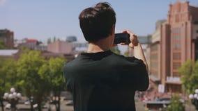 Retrovisione del turista irriconoscibile dell'uomo che fotografa citt? dallo smartphone stock footage