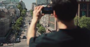Retrovisione del turista irriconoscibile dell'uomo che fotografa citt? dallo smartphone archivi video