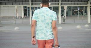 Retrovisione del turista maschio africano in cuffie che tirano il suo bagaglio mentre camminando verso l'aeroporto moderno metrag stock footage