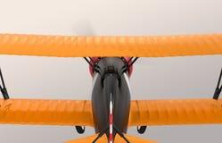 Retrovisione del volo giallo e nero del biplano nel cielo Immagine Stock