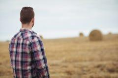 Retrovisione dell'agricoltore che sta nel campo Fotografia Stock Libera da Diritti