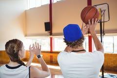 Retrovisione dell'allenatore giocatore di pallacanestro di addestramento in tribunale Immagine Stock