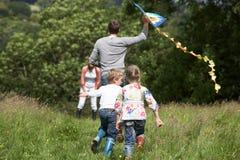 Retrovisione dell'aquilone di volo della famiglia in campagna Fotografie Stock