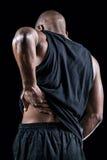 Retrovisione dell'atleta muscolare che soffre con il dolore alla schiena Fotografia Stock