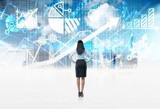 Retrovisione dell'integrale di una signora di affari che sta davanti ai precedenti finanziari digitali blu dei grafici Immagine Stock