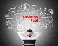 Retrovisione dell'uomo che esamina il disegno del business plan Immagine Stock Libera da Diritti