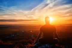Retrovisione dell'uomo che medita yoga nella posa del loto su roccia al tramonto Fotografia Stock