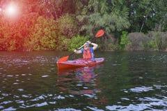 Retrovisione dell'uomo che rema kajak in lago con la donna nel fondo Coppia il kayak in lago un giorno soleggiato fotografia stock libera da diritti
