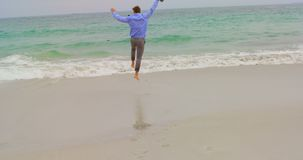 Retrovisione dell'uomo d'affari caucasico che corre con la giacca sportiva sulla spiaggia 4k archivi video