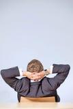 Retrovisione dell'uomo d'affari che si siede nell'ufficio con le mani dietro la testa fotografie stock