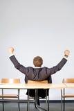 Retrovisione dell'uomo d'affari che si siede nell'ufficio con steso fotografia stock libera da diritti