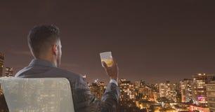 Retrovisione dell'uomo d'affari che si siede sulla sedia che tiene vetro di alcool e che esamina città fotografia stock libera da diritti