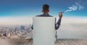 Retrovisione dell'uomo d'affari che si siede sulla sedia e che esamina mare mentre fumando sigaro Immagini Stock