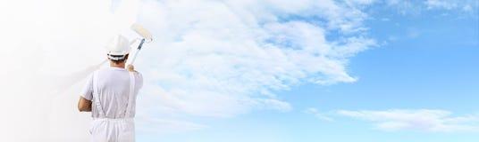 Retrovisione dell'uomo del pittore che dipinge il cielo blu sulla parete in bianco immagine stock