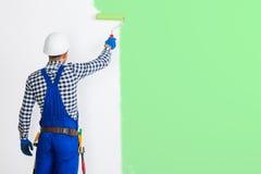Retrovisione dell'uomo del pittore che dipinge la parete nel verde immagini stock libere da diritti