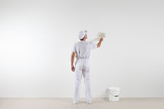 Retrovisione dell'uomo del pittore che esamina parete in bianco, con il pennello Fotografia Stock