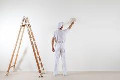 Retrovisione dell'uomo del pittore che guarda e che dipinge parete in bianco, con la p Fotografia Stock Libera da Diritti